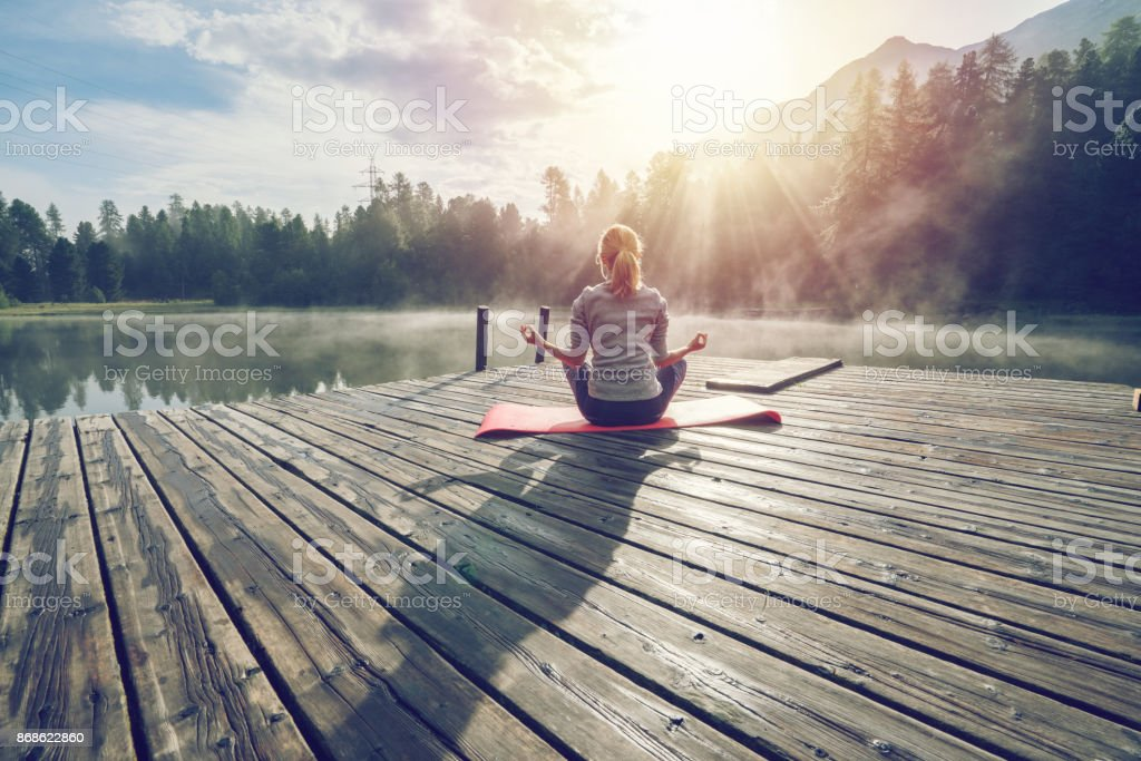 Caucasian girl exercising yoga in nature, morning by the lake in Switzerland stock photo