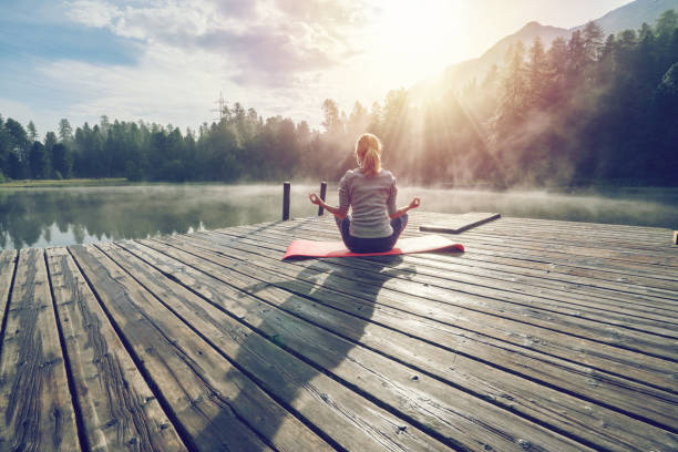 caucasian girl exercising yoga in nature, morning by the lake in switzerland - health and beauty stock photos and pictures