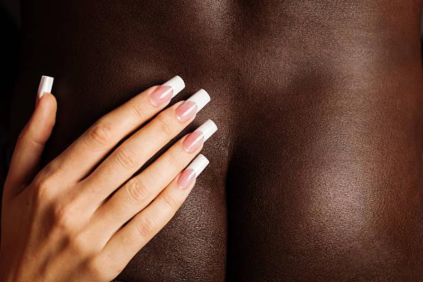 Caucasian girl grabbed the buttocks of black men by hand stock photo