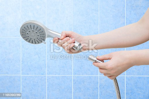 istock Caucasian girl holding in her hands a watering can for a shower and a bath and a metal hose. Close-up. 1165390289