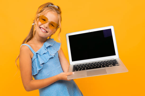 caucasian girl with a laptop shows a screen with mockup on an orange background - girl study home laptop front imagens e fotografias de stock