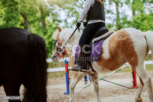Caucasian girl with helmet and protective vest on riding cute white and brown pony horse. Sunny day on ranch concept.