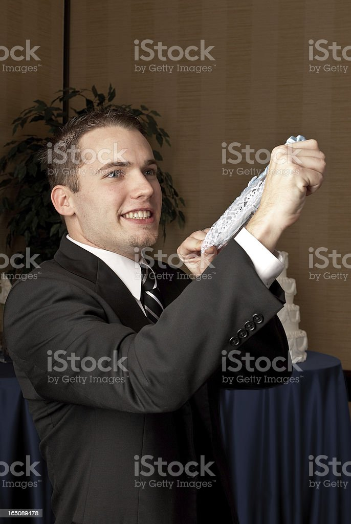 Caucasian groom flipping a garter belt stock photo