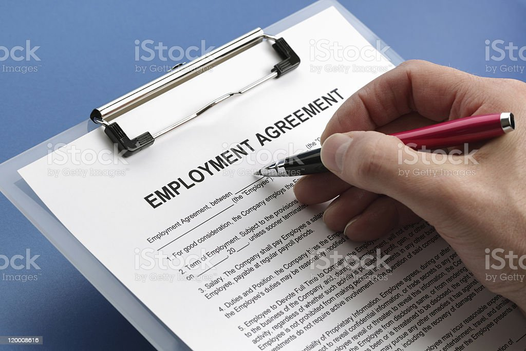 Caucasian hand filling out an employment agreement contract stock photo