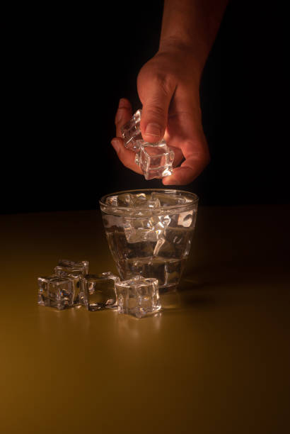 Caucasian hand pouring ice cubes into a glass of water - foto stock