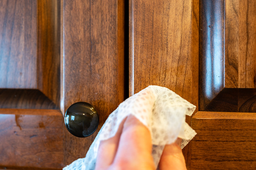 Caucasian hand with sanitizing wipe being used to disinfect a cabinet knob