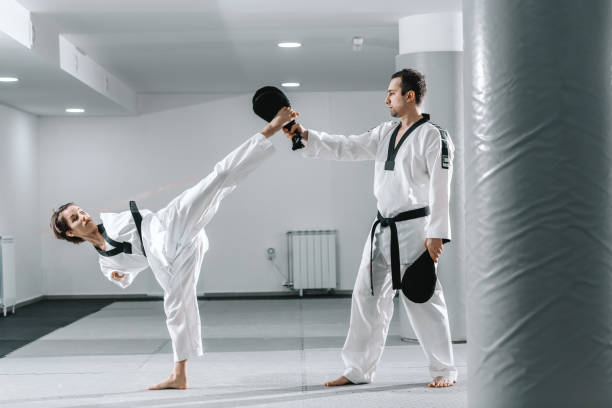 彼女の訓練でテコンドーを練習白人障害者の意欲的な女の子。キックターゲットを蹴る女の子。 - disabilitycollection ストックフォトと画像