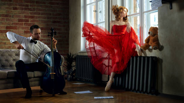 Caucasian handsome cellist visits the muse from fairytale in red dress stock photo