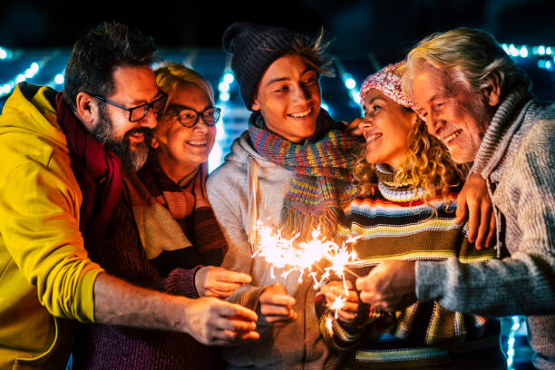 Caucasian happy family enjoy and celebrate by night with fire sparkler all together having fun - christmas and new year eve celebration for group of cheerful people mixed ages and generations stock photo