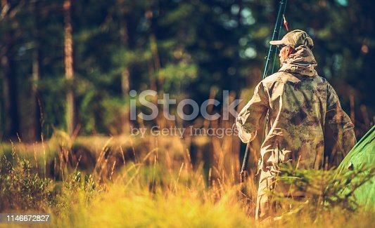 Caucasian Hunter in the Wild. Men in His 30s with Fishing Rod in Hand.