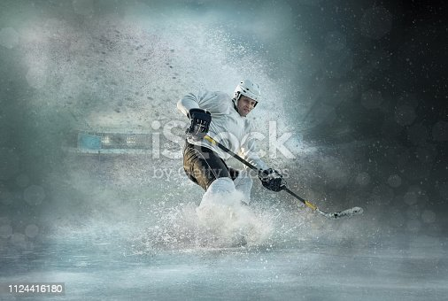 istock Caucasian ice hockey Players in dynamic action in a professional sport game play in hockey under stadium lights. 1124416180