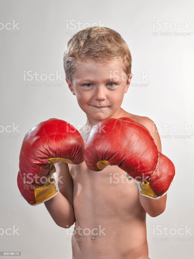Caucasian kid with red and yellow gloves stock photo