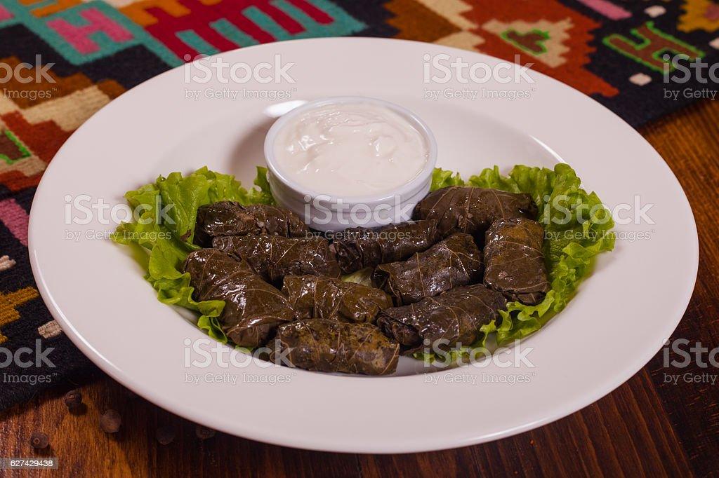 Caucasian kitchen. Dolma with sour cream on a white plate stock photo