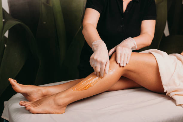 Caucasian lady with beautiful legs is having a sugar epilation during a professional spa procedure stock photo