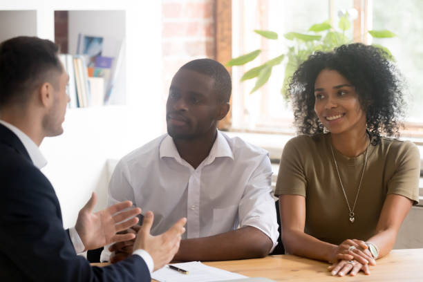 caucasian lawyer or financial advisor consulting young african couple - real estate law stock photos and pictures
