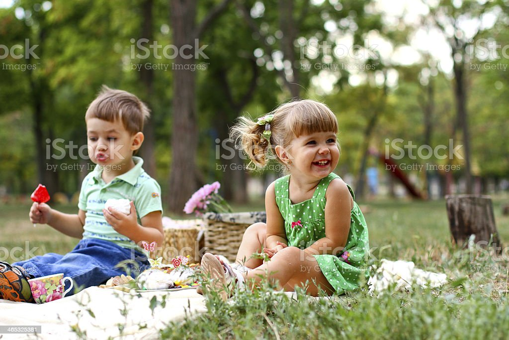 Caucasian little boy and girl eating sweets stock photo