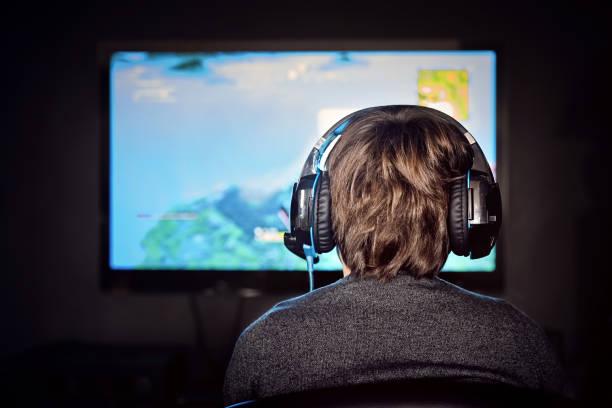kaukasische kleine gamer jongen het dragen van een headset speelt video game. video gameverslaving. - gaming stockfoto's en -beelden