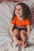 Caucasian little girl with lush hair laughing while sitting on bed 2021