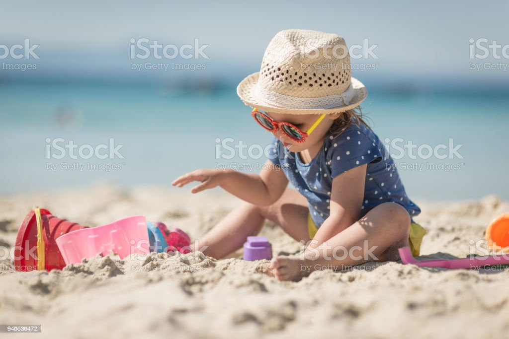 Caucasian littplayng beach toysle girl with hat - Royalty-free Alegria Foto de stock