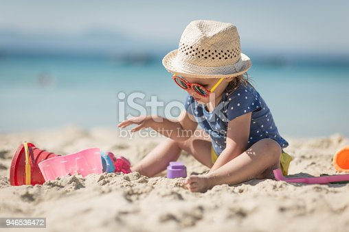 Caucasian littplayng beach toysle girl with hat