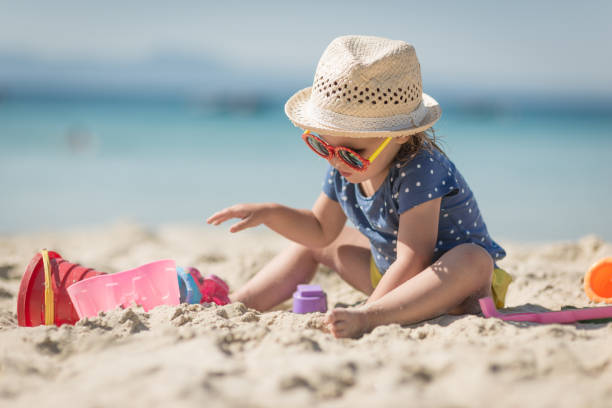 Caucasian littplayng beach toysle girl with hat stock photo
