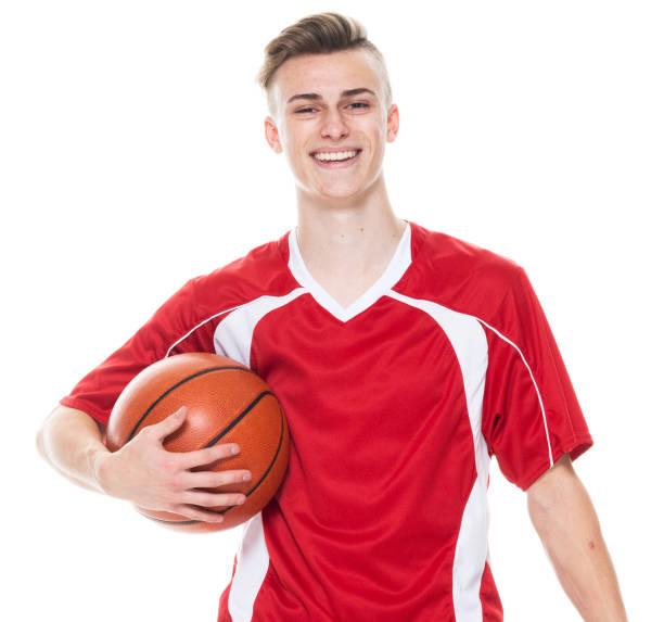Kaukasische männliche American-Football-Spieler stehen vor weißem Hintergrund in Fußball-Uniform und halten Basketball - Ball und Fußball spielen - Sport und mit Sportball – Foto
