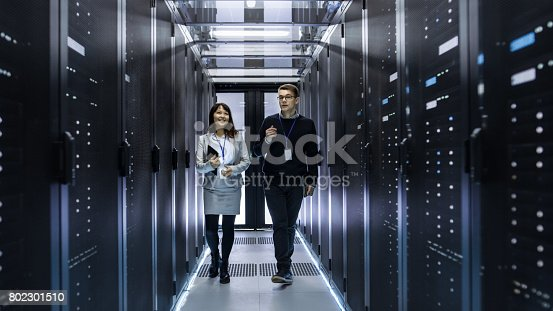 istock Caucasian Male and Asian Female IT Technicians Walking through Corridor of Data Center with Rows of Rack Servers. They Have Discussion, She Holds Tablet Computer. 802301510