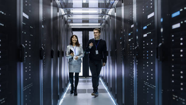 caucasian male and asian female it technicians walking through corridor of data center with rows of rack servers. they have discussion, she holds tablet computer. - network server stock pictures, royalty-free photos & images