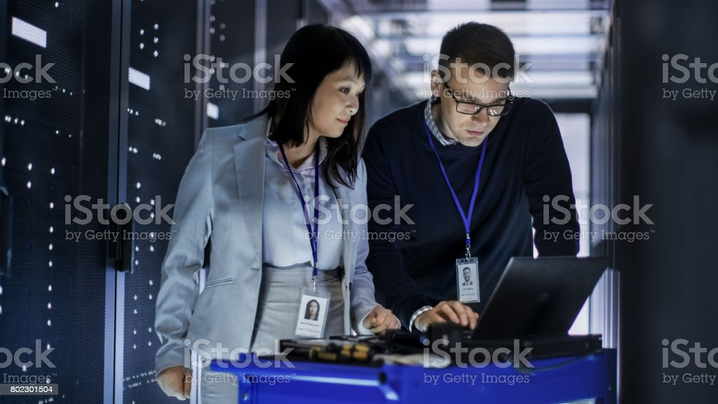 Caucasian Male and Asian Female IT Technicians Working with Computer Crash Cart in Big Data Center full of Rack Servers. royalty-free stock photo