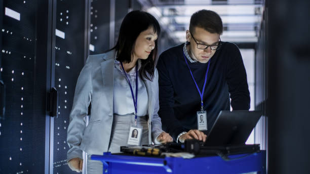 Caucasian Male and Asian Female IT Technicians Working with Computer Crash Cart in Big Data Center full of Rack Servers. stock photo
