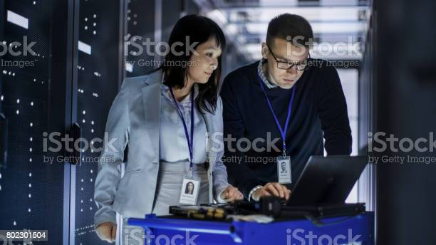 Caucasian Male And Asian Female It Technicians Working With Computer Crash Cart In Big Data Center Full Of Rack Servers Stock Photo - Download Image Now