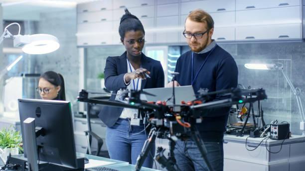 ingenieros de mujeres negras y masculinas caucásicas que trabajan en un proyecto de drones con la ayuda de un ordenador portátil y notas. trabaja en un laboratorio moderno de alta tecnología brillante. - robótica fotografías e imágenes de stock