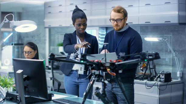 ingenieros de mujeres negras y masculinas caucásicas que trabajan en un proyecto de drones con la ayuda de un ordenador portátil y notas. trabaja en un laboratorio moderno de alta tecnología brillante. - ingeniero fotografías e imágenes de stock