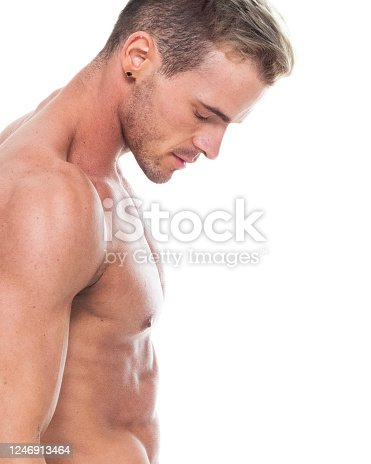 One person of aged 20-29 years old caucasian male athlete standing in front of white background who is toughness and showing flexing muscles who is barefoot and being active with body building