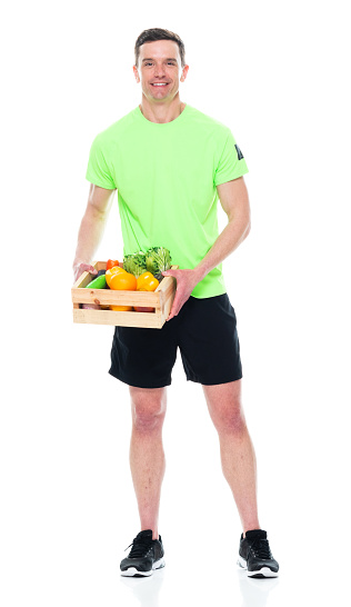 Caucasian male athlete standing in front of white background wearing running shorts and holding basket