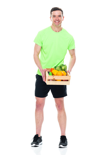 Caucasian male athlete standing in front of white background wearing t-shirt and holding container