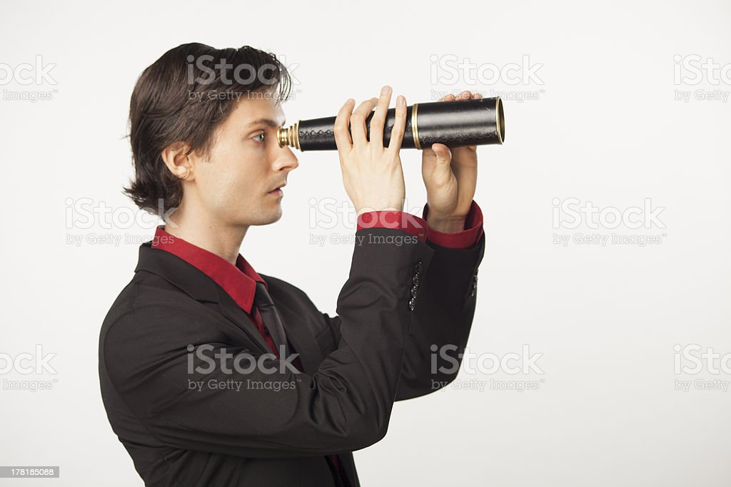 Caucasian male business man in suit holding telescope stock photo