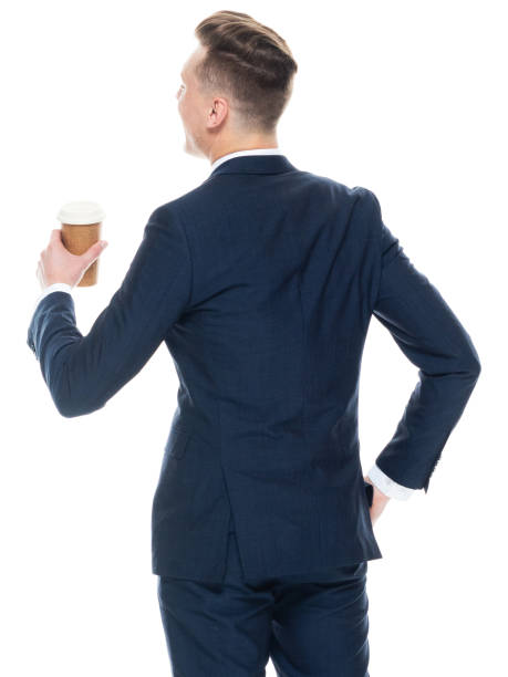 Caucasian male business person standing in front of white background wearing businesswear and holding coffee cup stock photo
