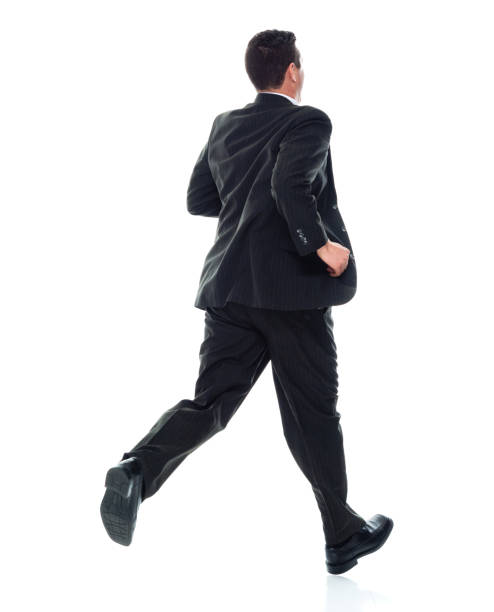 Caucasian male businessman jogging in front of white background wearing businesswear stock photo