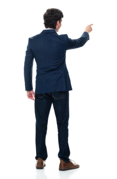 Caucasian male businessman standing in front of white background wearing jeans stock photo