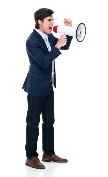 Caucasian male businessman standing in front of white background wearing blazer and holding megaphone stock photo