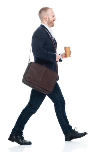 Kaukasischer männlicher Geschäftsmann zu Fuß vor weißem Hintergrund trägt Umhängetasche und Haltetasche – Foto