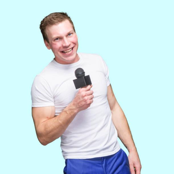 Kaukasischer männlicher Kommentator steht vor blauem Hintergrund, trägt Hemd und Mikrofon – Foto