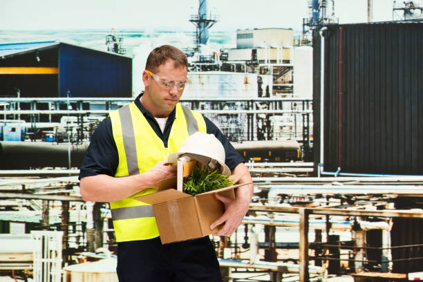Caucasian male construction worker wearing reflective clothing and holding cardboard box stock photo