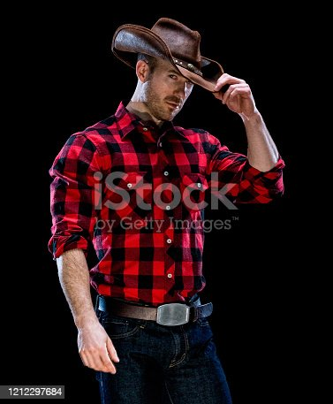 Portrait of aged 30-39 years old caucasian male cowboy standing in front of black background wearing button down shirt who is of muscular build