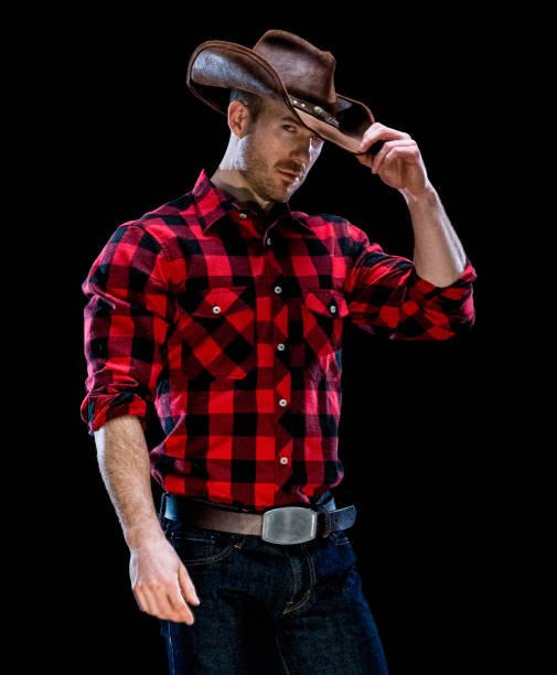 Caucasian male cowboy standing in front of black background wearing button down shirt stock photo