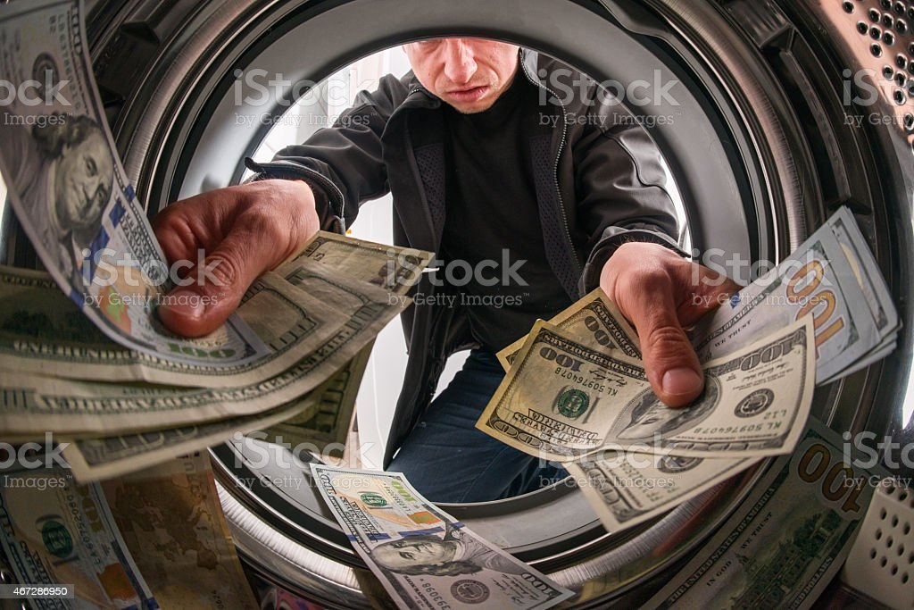 Caucasian male criminal throwing money inside a laundry machine stock photo