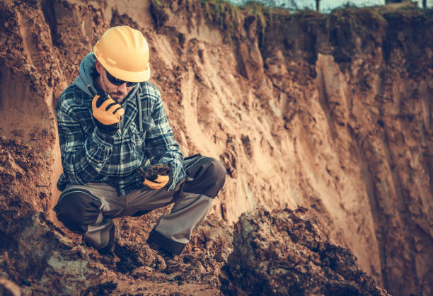 Caucasian Male Engineering Geologist Talking On Radio At Construction Site. stock photo