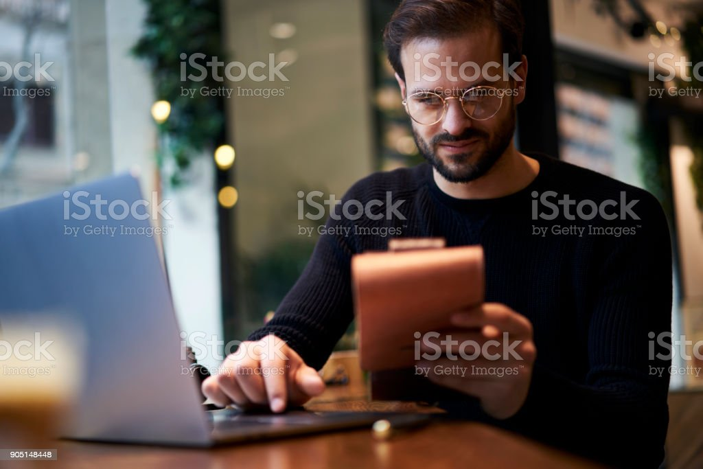 Caucasian male freelancer accounting and reading financial news while using digital devices and notebook. Cropped image of young business man working in coffee shop while sitting at wooden table stock photo