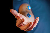 Caucasian male hand throwing blue dice cubes in the air - closeup with shallow focus